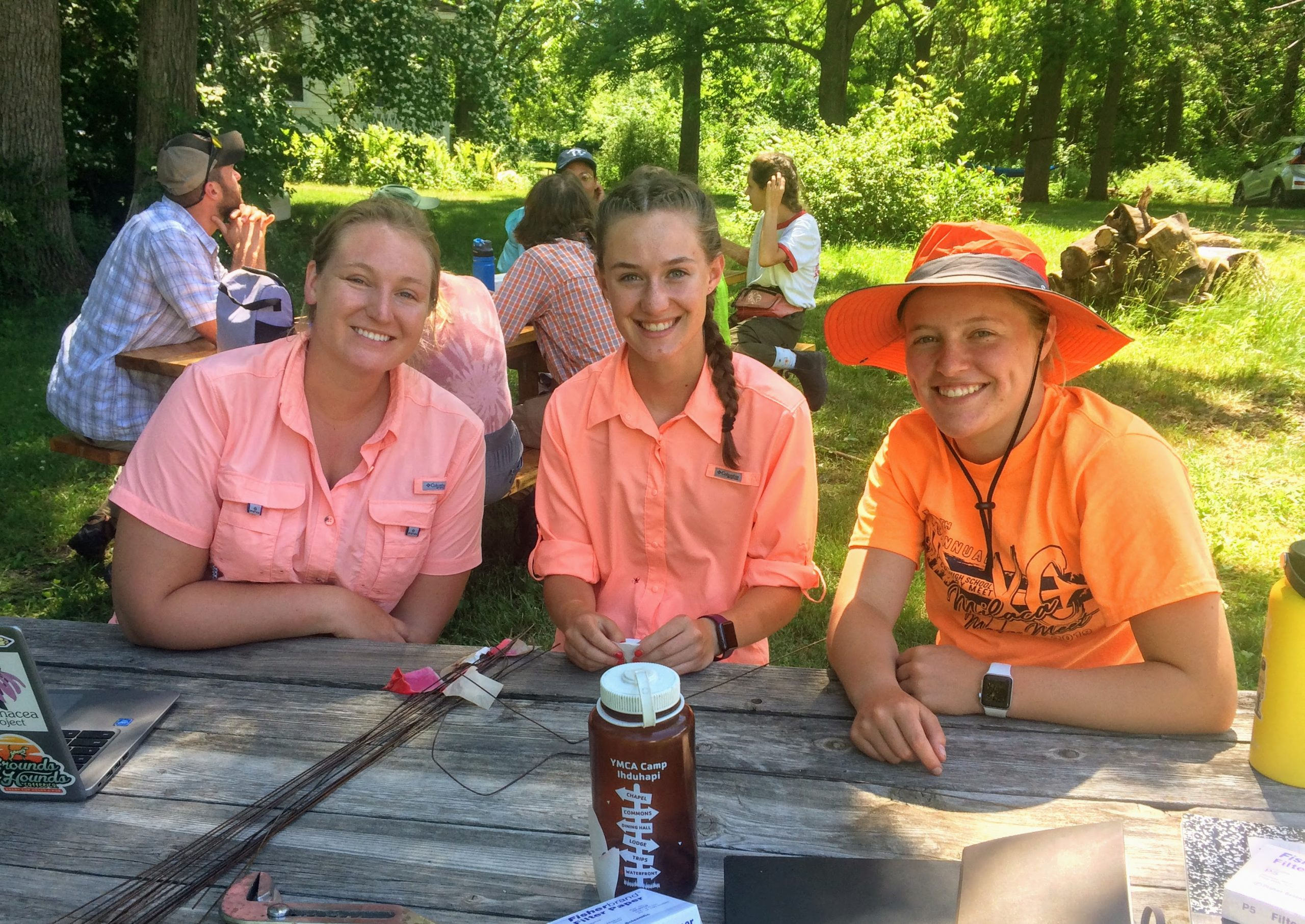 Team Dust! Alex, Emma, and Kennedy wearing sunset colored shirts at the picnic table.